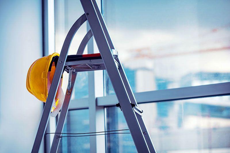 Een ladder met daaraan een gele werkhelm, daarachter is een wazige raam zichtbaar.